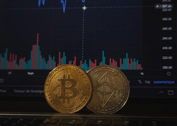 Featured image for bitcoin price decline story showing two bitcoins placed near a screen