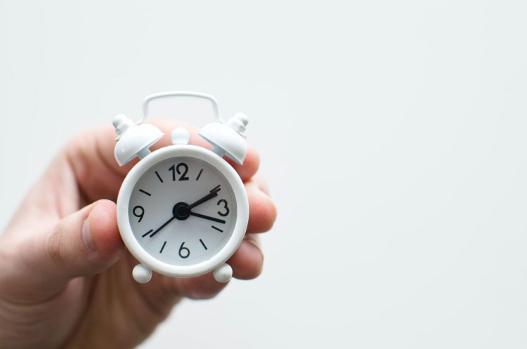 A person holding a white alarm clock