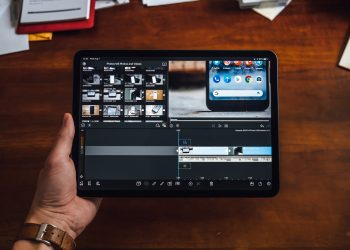 A person holding an iPad Pro while editing a video on it